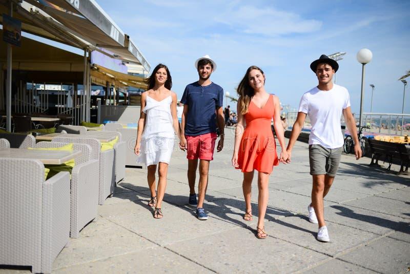Groupe do homem e da mulher dos jovens que andam no beira-mar do recurso turístico durante o dia de verão ensolarado imagens de stock royalty free