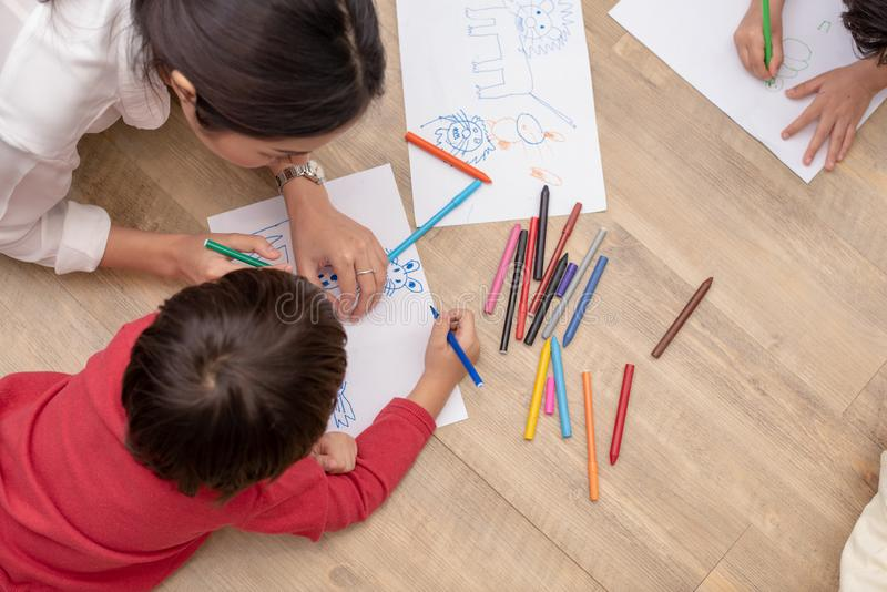 Groupe du dessin pr?scolaire d'?tudiant et de professeur sur le papier dans la classe d'art De nouveau ? l'?cole et au concept d' photos libres de droits
