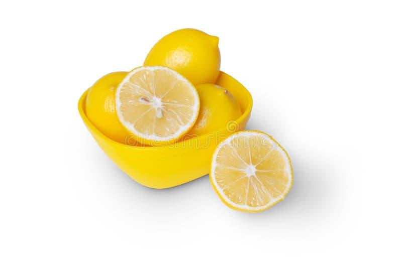 Groupe entier d'agrumes de citron jaune mûr avec un demi-fruit de citron dans une marmite jaune isolé sur fond blanc avec cheminé photos stock