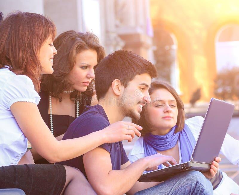 Groupe gai d'?tudiants souriant et regardant un ordinateur portable images stock