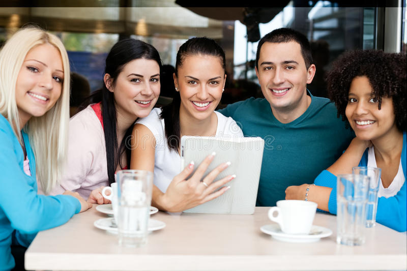 Groupe heureux d'adolescents avec le comprimé photographie stock libre de droits