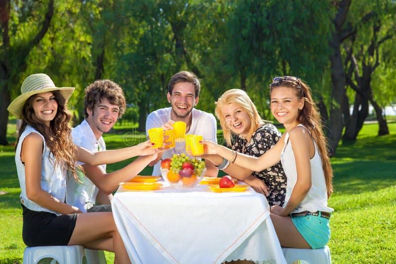 Groupe heureux d'adolescents soulevant un pain grillé photo libre de droits