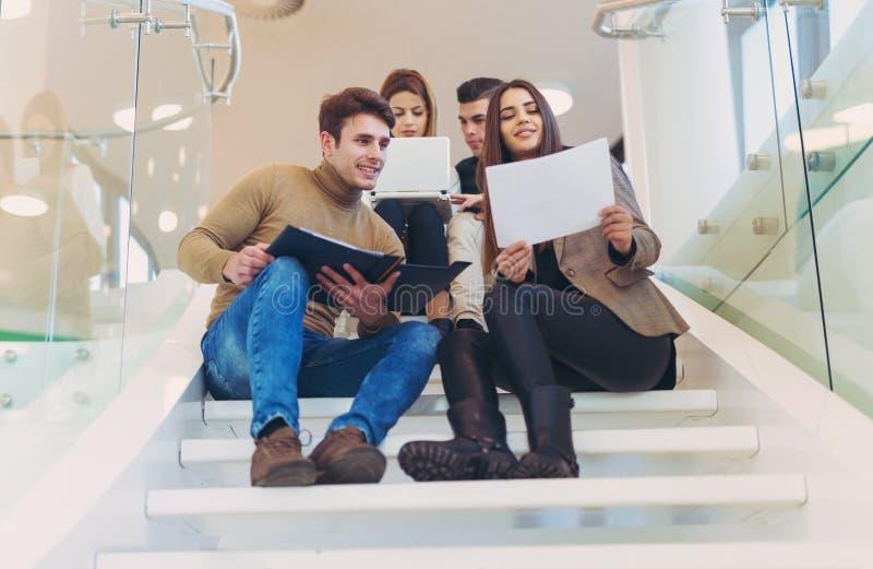 Groupe heureux d'amis s'asseyant sur les escaliers dans l'école photos stock
