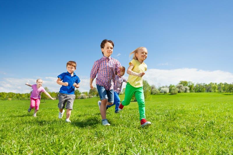 Groupe heureux d'enfants courant en parc vert photos libres de droits