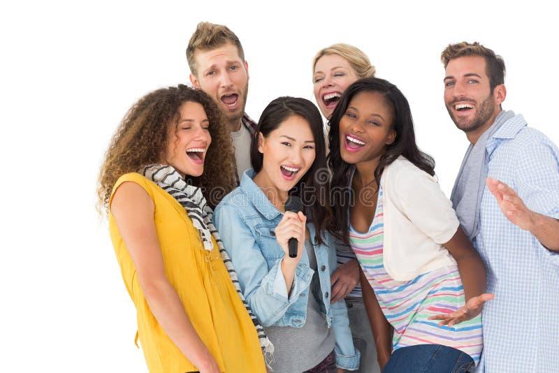 Groupe heureux de jeunes amis ayant l'amusement faisant le karaoke photos libres de droits