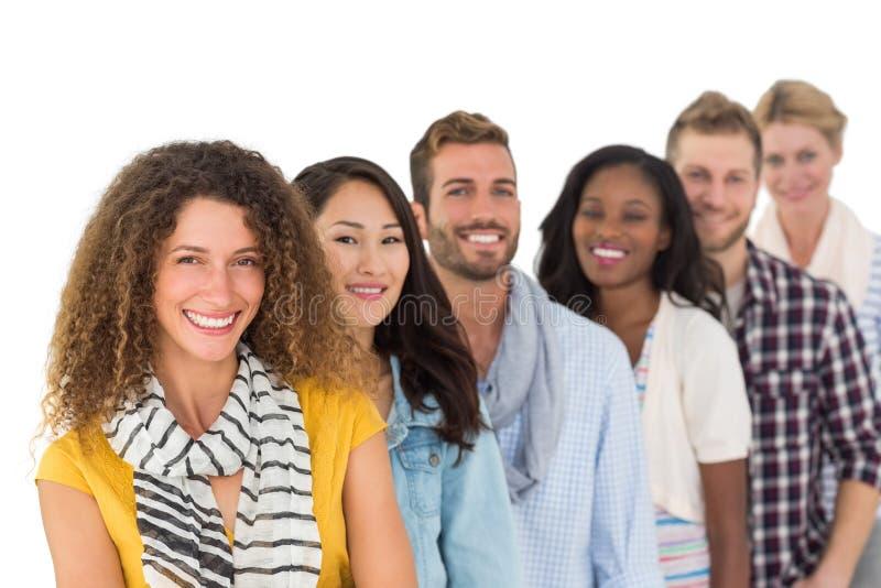 Groupe heureux de jeunes amis se tenant dans une rangée photos libres de droits