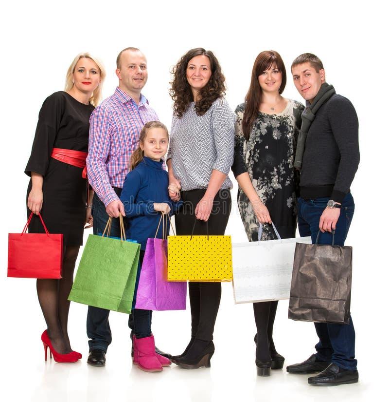 Groupe heureux de personnes d'achats tenant des sacs photographie stock libre de droits