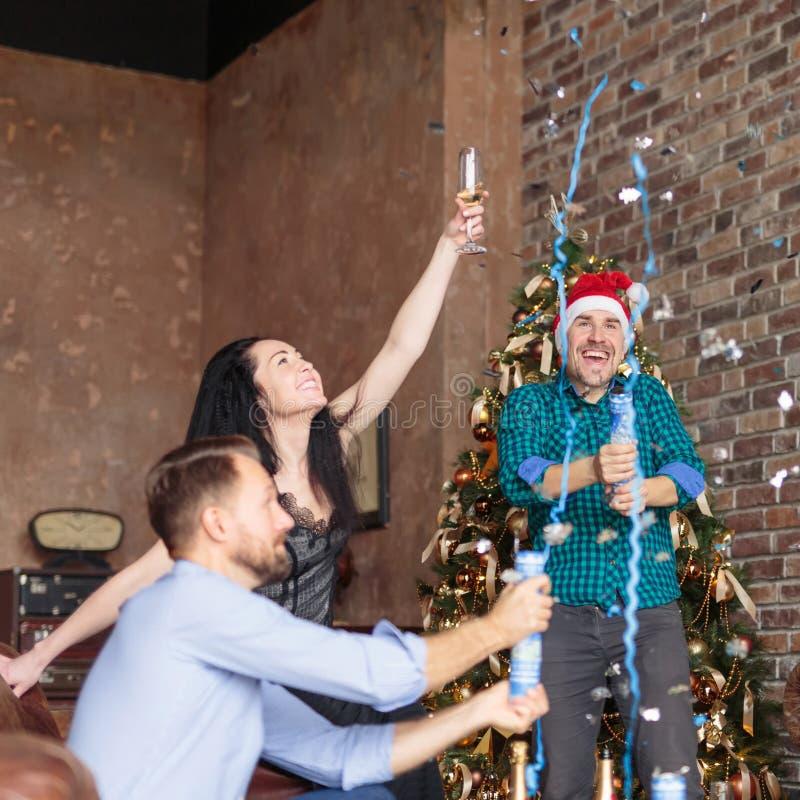 Groupe heureux de trois amis qui s'amusent avec des confettis et du champagne à la fête du Nouvel An image stock