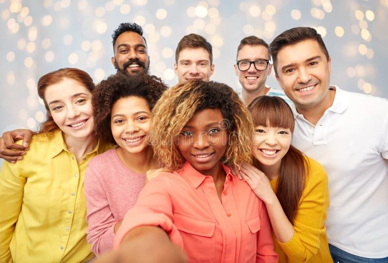 Groupe international de personnes heureuses prenant le selfie photos stock