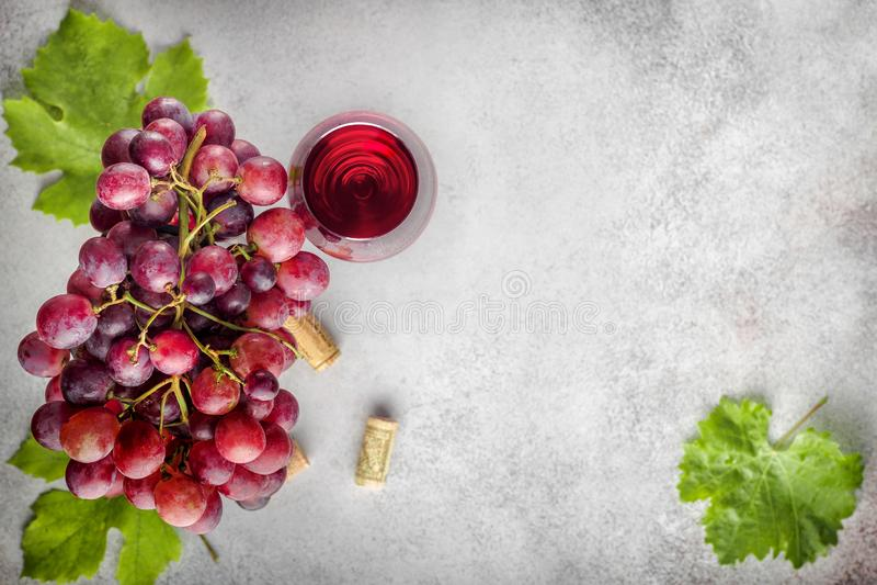 Groupe mûr de raisin avec les feuilles et le verre de vin sur le backgro en pierre photos stock