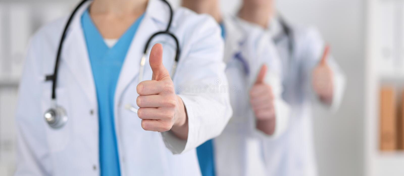 Groupe of medicine doctors show OK sign with thumb up close up. Success and high level service in health care, best. Treatment and customer loyalty and physical stock photography