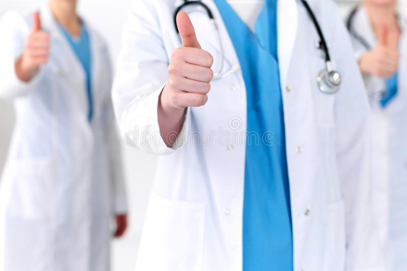 Groupe of medicine doctors show OK sign with thumb up close up. Success and high level service in health care, best. Treatment and customer loyalty and physical royalty free stock photography