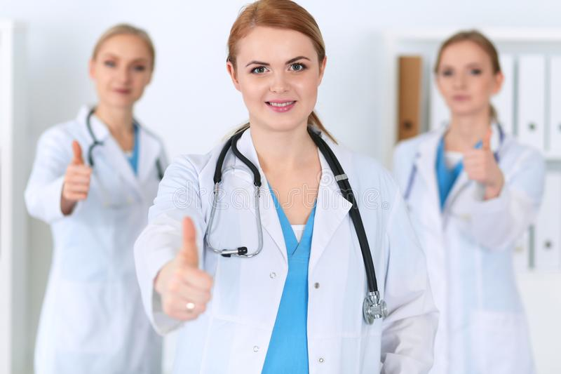 Groupe of medicine doctors show OK sign with thumb up. Success and high level service in health care, best treatment and. Customer loyalty and physical concept stock photography