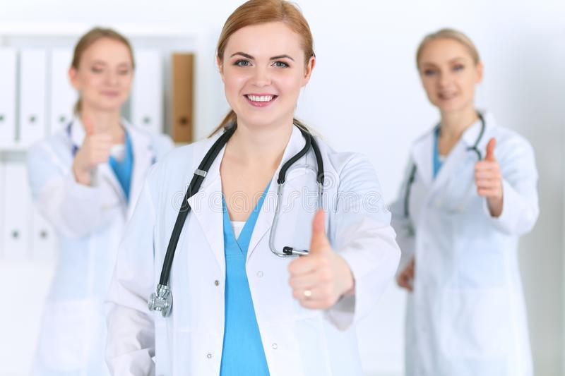 Groupe of medicine doctors show OK sign with thumb up. Success and high level service in health care, best treatment and. Customer loyalty and physical concept stock images