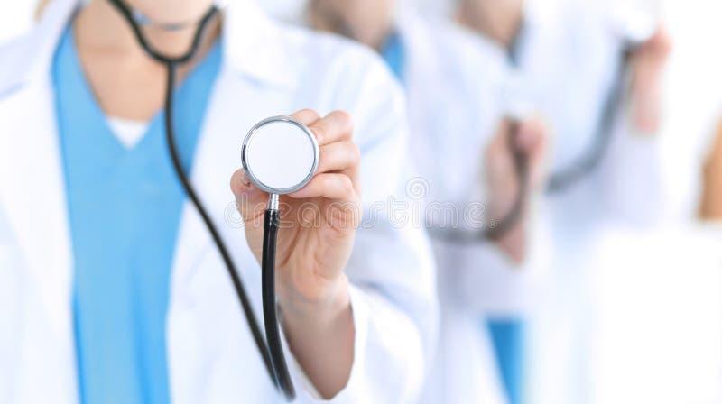 Groupe medycyn lekarki trzyma stetoskop głowy zbliżenie Lekarzi przygotowywający egzamininować pacjenta i pomagać pomoc medyczna zdjęcia royalty free