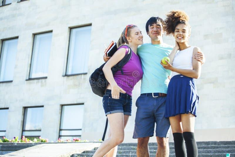 Groupe mignon de teenages au b?timent de l'universit? avec des huggings de livres, mode de vie d'?tudiants de nations de diversit photo stock