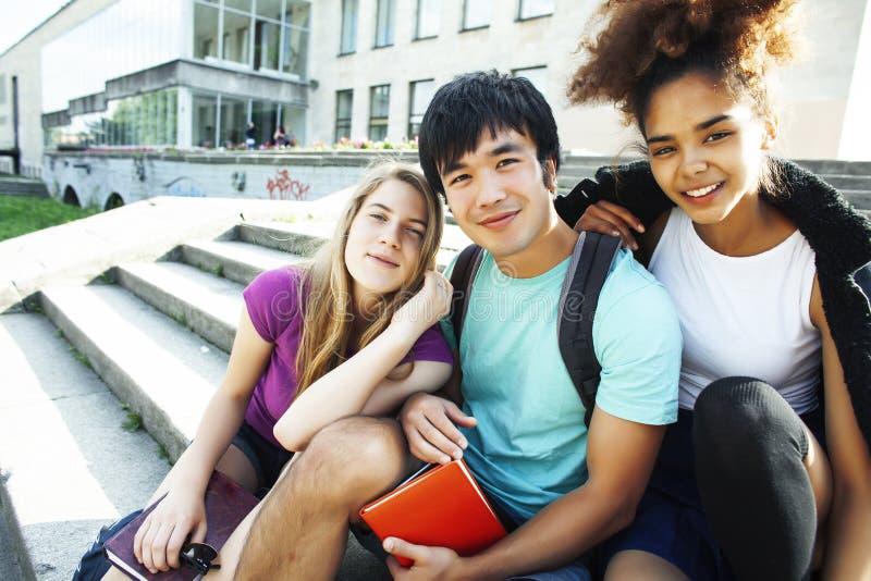 Groupe mignon de teenages au b?timent de l'universit? avec des huggings de livres, mode de vie d'?tudiants de nations de diversit image libre de droits