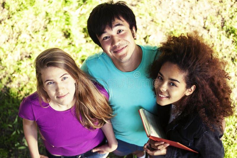 Groupe mignon de teenages en parc vert à l'été avec des huggings de livres, mode de vie d'étudiants de nations de diversité vrai photo stock
