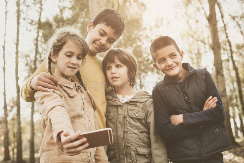Groupe moyen d'enfants faisant l'autoportrait Fixation de petite fille photos stock