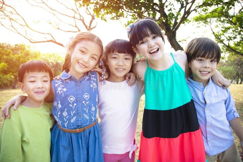 Groupe multi-ethnique d'écoliers en parc photographie stock