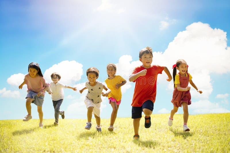 Groupe multi-ethnique d'écoliers riant et courant photographie stock