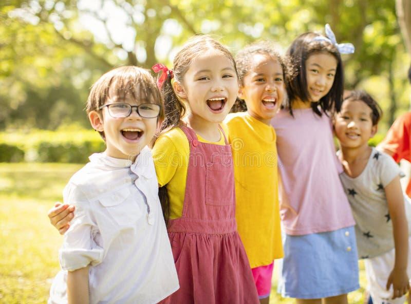 Groupe multi-ethnique d'écoliers riant et embrassant photo stock