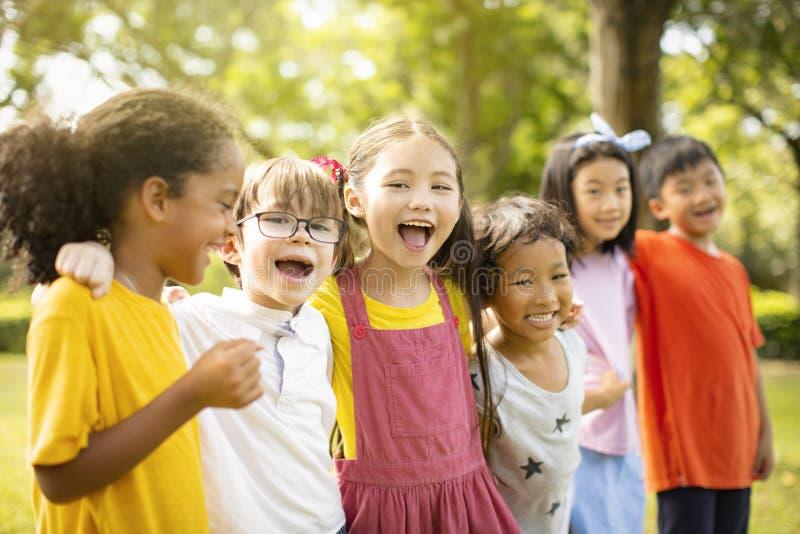 Groupe multi-ethnique d'écoliers riant et embrassant image stock