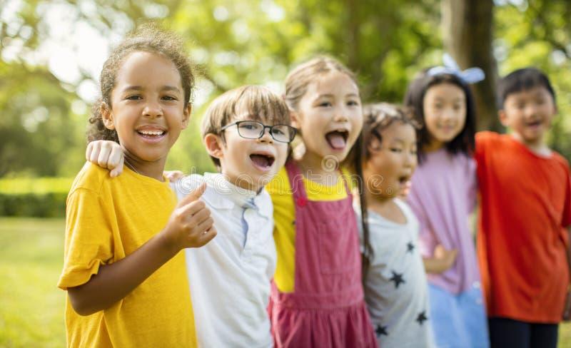 Groupe multi-ethnique d'écoliers riant et embrassant photographie stock