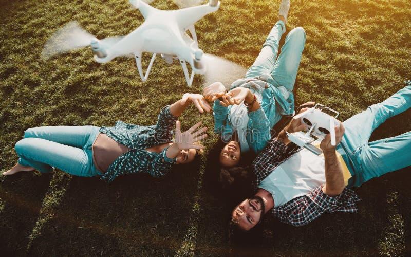 Groupe multi-ethnique d'amis sur le herbe-complot avec le multiro image libre de droits