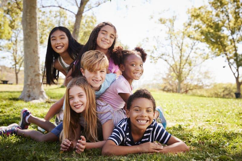 Groupe multi-ethnique d'enfants se trouvant sur l'un l'autre en parc photographie stock