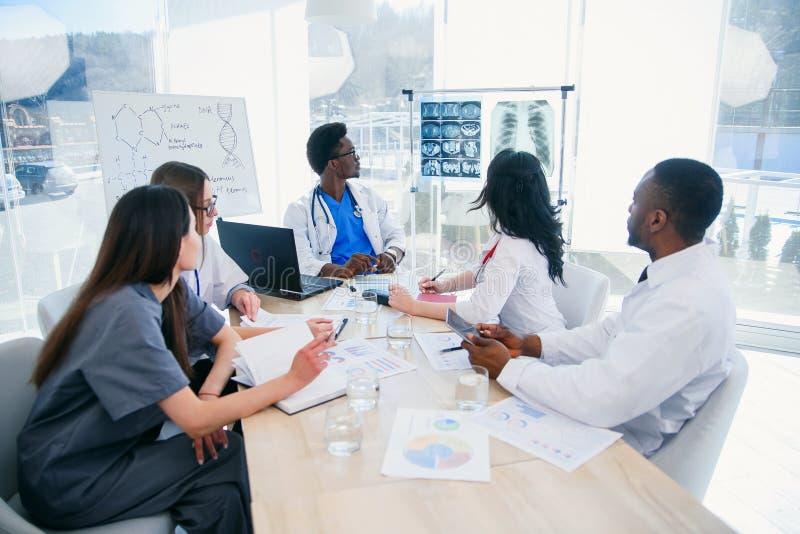 Groupe multi-ethnique de médecins professionnels discutant des copies de rayon X de patient dans le lieu de réunion à l'hôpital m photographie stock libre de droits
