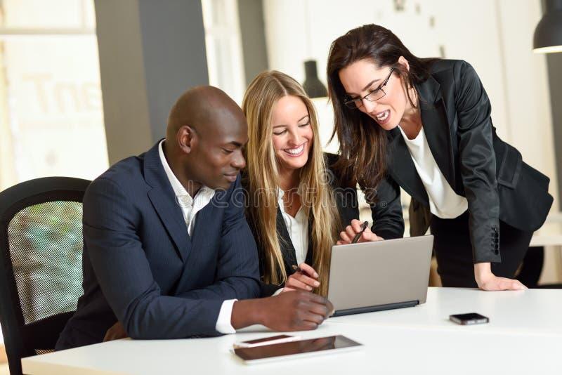 Groupe multi-ethnique de trois hommes d'affaires se réunissant dans un o moderne photo stock