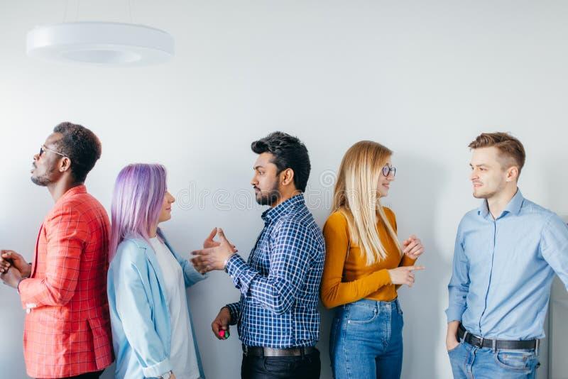 Groupe multi-ethnique des jeunes dans la tenue de détente au-dessus du fond gris photos stock