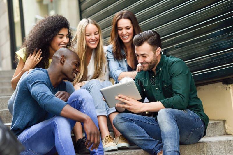 Groupe multi-ethnique des jeunes regardant une tablette images libres de droits