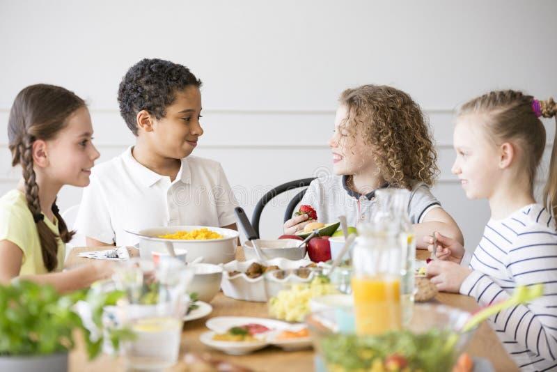Groupe multiculturel de sourire d'enfants mangeant de la nourriture images libres de droits