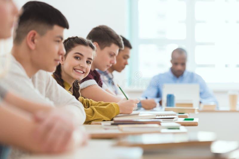 Groupe multiculturel des étudiants adolescents et du professeur de lycée au bureau avec l'ordinateur portable dans la salle de cl images libres de droits