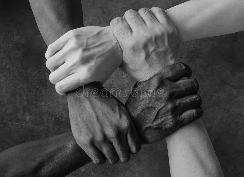 Groupe multiracial avec les mains caucasiennes d'africain noir et asiatiques américaines se tenant poignet dans l'amour d'unité d images libres de droits