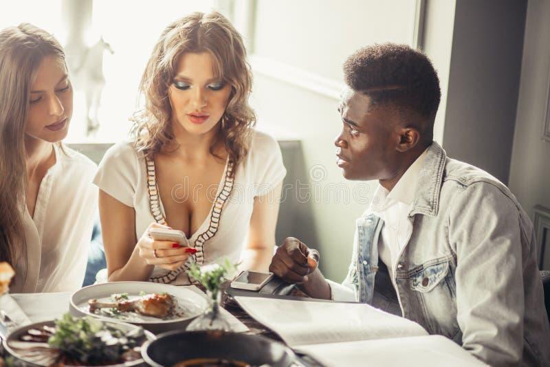 Groupe multiracial d'amis prenant le déjeuner ensemble Deux femmes européennes et un type africain au café photographie stock