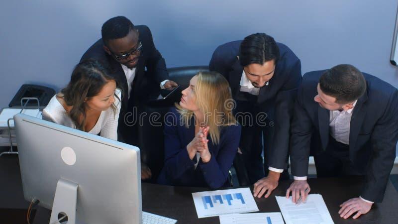 Groupe multiracial de gens d'affaires gais discutant l'infographics analytique tout en ayant fulminer de cerveau dans photo libre de droits