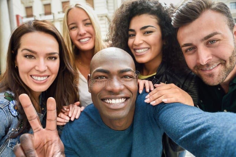 Groupe multiracial des jeunes prenant le selfie images stock