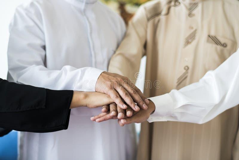 Groupe musulman d'amis empilant des mains photographie stock