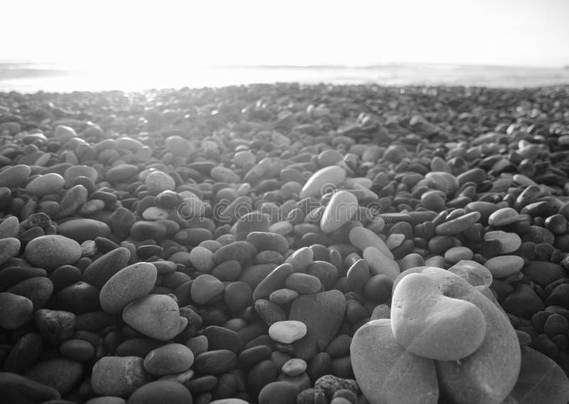 Groupe noir et blanc Grey Stones qui est un dans en forme de coeur à une plage en île du sud Nouvelle-Zélande image stock
