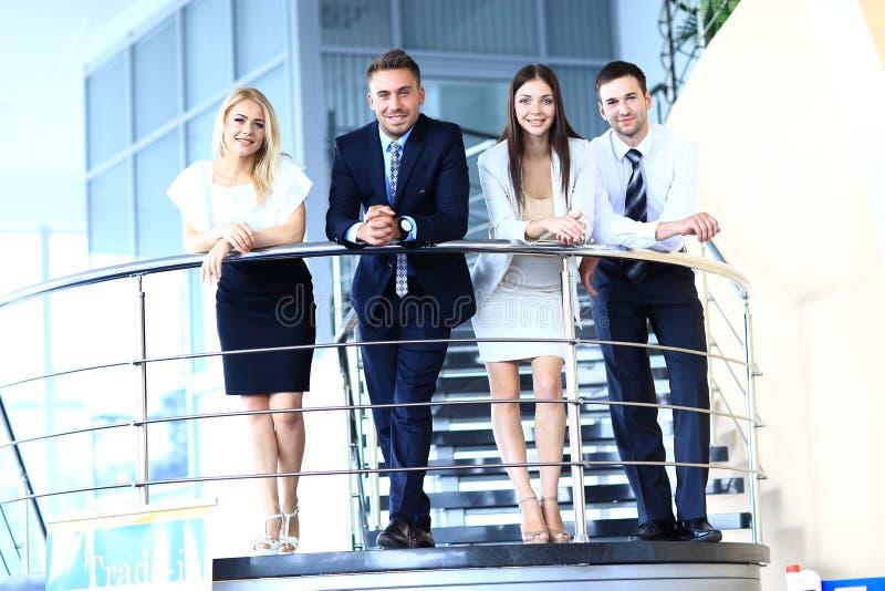 Groupe positif d'affaires se tenant sur des escaliers de bureau moderne images stock
