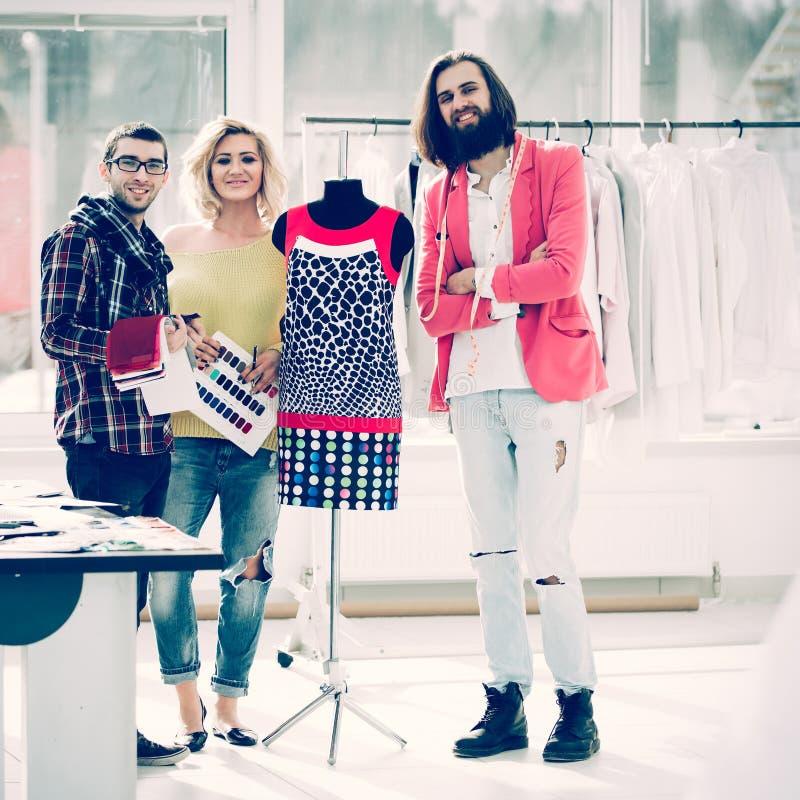 Groupe pour des couturiers dans le studio sur un fond de nouveau mod photographie stock libre de droits
