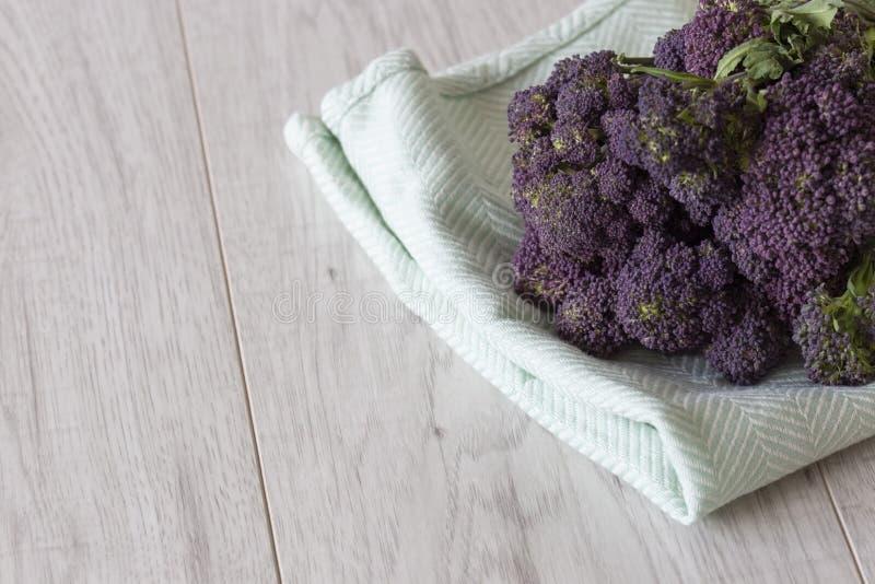 Groupe pourpre de brocoli sur une serviette de th? vert photo libre de droits