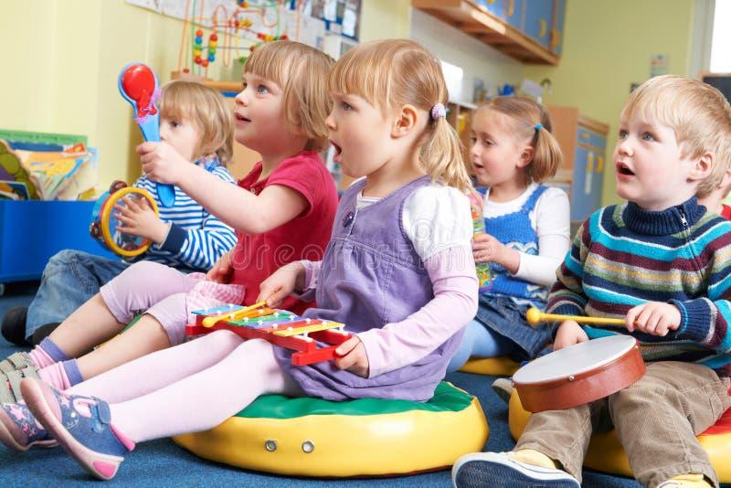 Groupe pré d'écoliers participant à la leçon de musique photographie stock