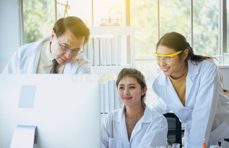 Groupe projet de recherches d'étudiant en médecine d'Asiatiques du nouveau avec le professeur supérieur ensemble au laboratoire images libres de droits