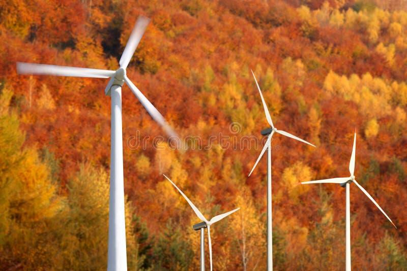 Groupes électrogènes de moulins de vent contre la forêt d'automne images stock
