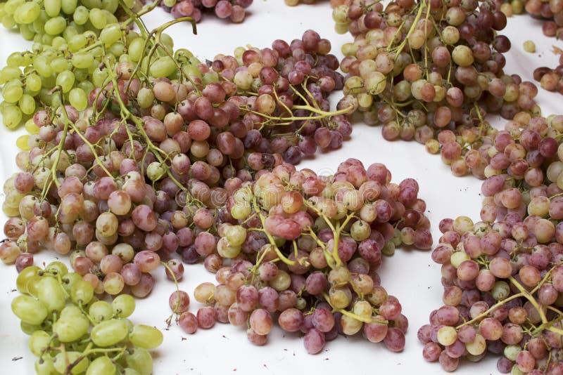 groupes de raisins roses sur la table blanche image libre de droits