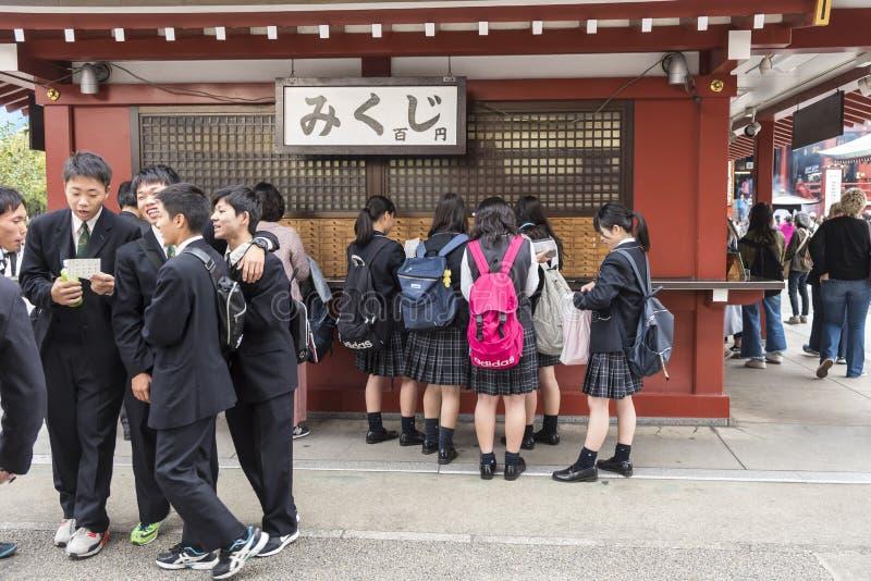 Groupez les écoliers et les filles d'o achetant l'omikuji la fortune de papier Sensoji Tokyo photographie stock libre de droits